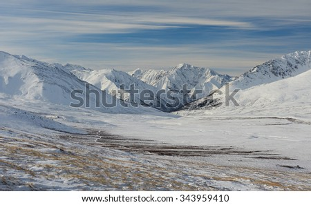 Winter landscape. Dramatic overcast sky.Severe mountains peaks covered by snow. Russia, Siberia, Altai mountains, Chuya ridge. - stock photo