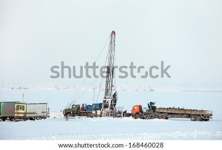 winter landscape drilling in snowy field and pump on the horizon in a haze - stock photo