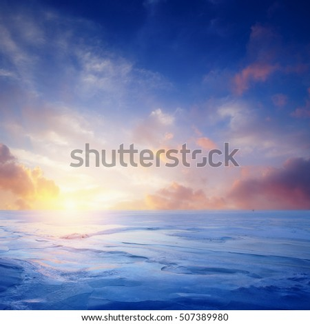 Winter landscape. Frozen sea and beautiful sunset sky. Sunlight reflected on the ice