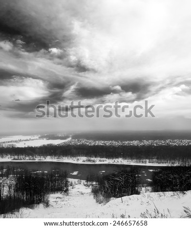 Winter landscape. Gray snowy forest and blue sky with white clouds. Cold river. Black and white photo - stock photo