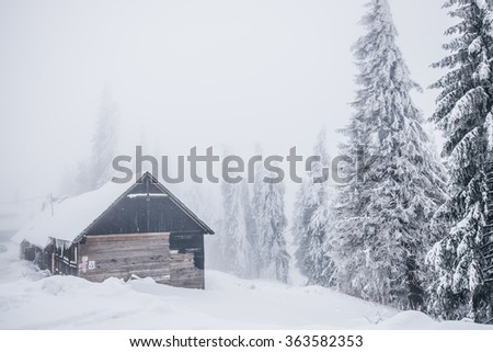 winter landscape in mountains with little house