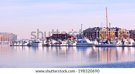 Winter landscape of Baltimore Inner Harbor. Yachts anchored at pier in winter. - stock photo