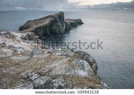 Winter landscape of Neist Point on Isle of Skye, Scotland, Snow, clouds, ocean and cliff - secluded Highlands of Scotland.