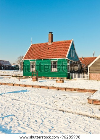 Winter landscape of old dutch village in snow on beautiful clear day. Blue sky.