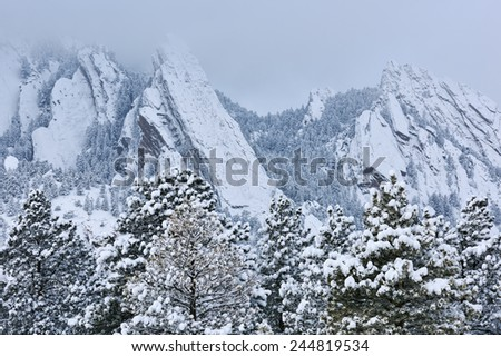 Winter landscape of the Flatirons flocked with snow, Rocky Mountains, Boulder, Colorado, USA  - stock photo