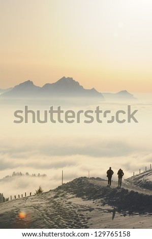 Winter landscape on the mountain Rigi, in Switzerland, with two hikers in the foreground, with mountain Pilatus in the background - stock photo
