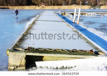 Winter landscape or seascape with floating bridge frozen solid in the sea ice. Frost cover the pier. Unknown person visible in background. Listerby, Sweden. - stock photo