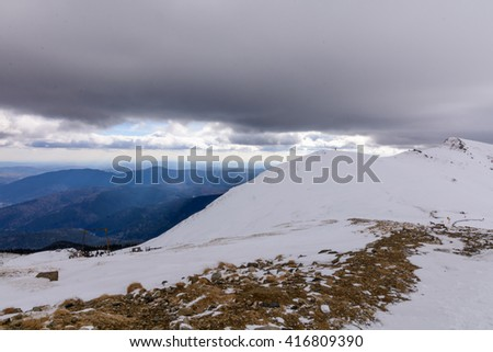 Winter landscape over Carpathian Mountains, Romania. Stunning winter scenery in Carpathian Mountains ridge on touristic plateau. - stock photo