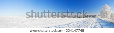 winter landscape, panorama with a field and the city - stock photo
