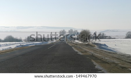 winter landscape paved road leading to the horizon and snow-covered fields - stock photo