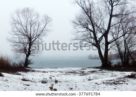 Winter landscape. River bank in evening mist. Sad winter mood