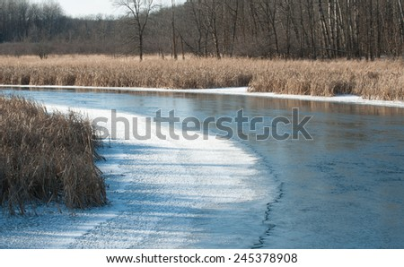 Winter landscape: Scenic bend in a partly frozen river channel - stock photo