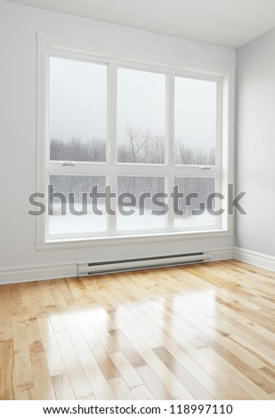 Winter landscape seen through the big window of an empty room. - stock photo