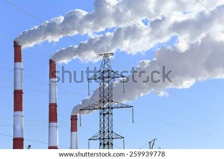 winter landscape smoke from the chimneys Zainsk TPP against the blue sky frosty misty morning - stock photo