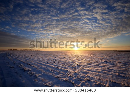 winter landscape snow-covered fields and roads in sunlight rays on the sunset