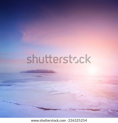 winter landscape, sunrise over frozen river with a beautiful clouds on sky