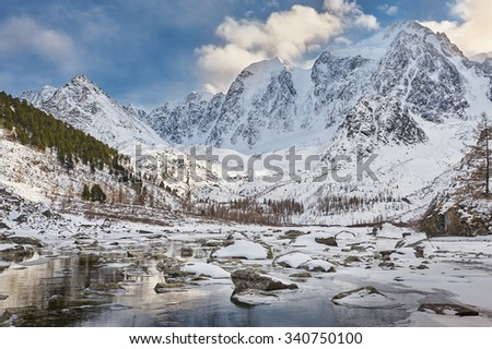 Winter landscape. The remains are not of a frozen lake. Severe mountains peaks covered by snow. Russia, Siberia, Altai mountains, Chuya ridge. - stock photo