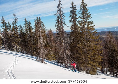 Winter landscape with a mountain ski tracks and tourist back country skier