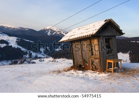 Winter landscape with a wooden watch-box next to the alpine skiing track in the mountains