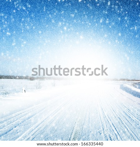Winter landscape with country road, sky and snowfall. - stock photo