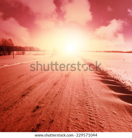 Winter landscape with empty country road at sunset. - stock photo