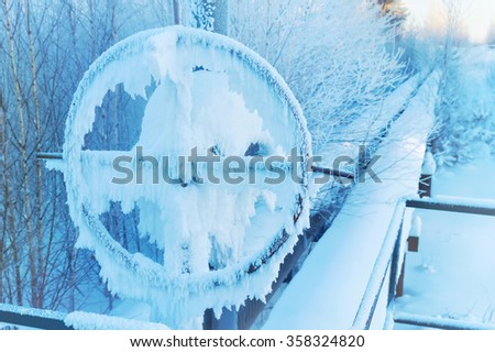 Winter landscape with frosted pipeline and valve - stock photo