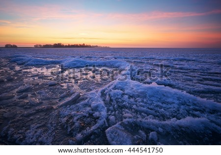 Winter landscape with frozen lake and sunset fiery sky. Composition of nature.   - stock photo