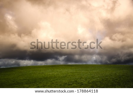 winter landscape with green field and storm clouds