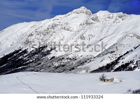 winter landscape with hut and blue sky - stock photo