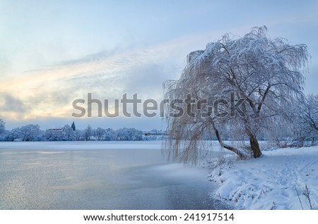 Winter landscape with lake and trees covered with frost - stock photo