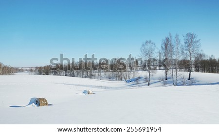 Winter landscape with rolls of hay on the snowy field - stock photo
