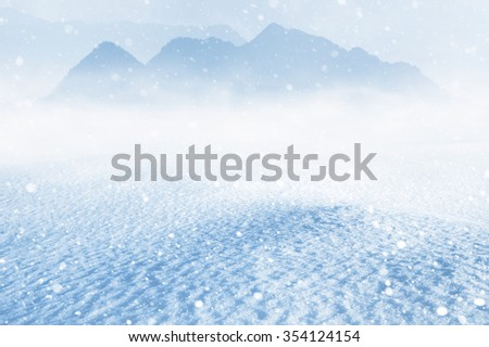 Winter landscape with snow drifts and mountains in the background - stock photo
