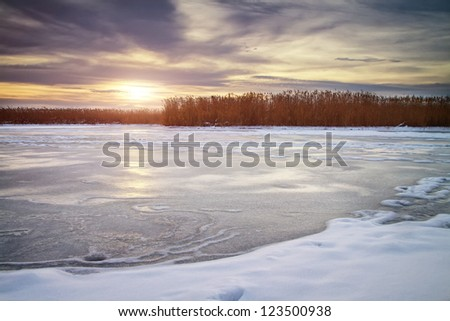 Winter landscape with sun and frozen river. Daybreak