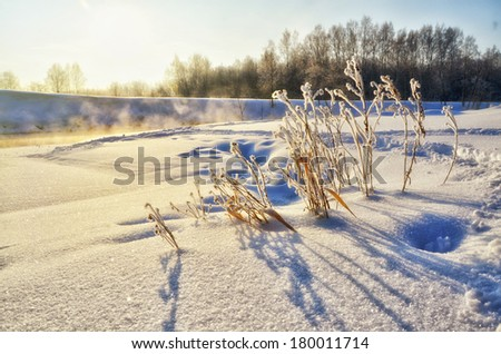 Winter landscape with sun and frozen river in sunset