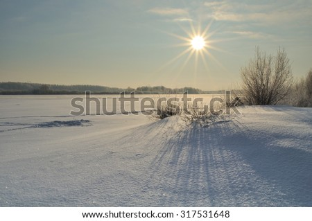 Winter landscape with the frozen river  at the sunset - focus at the frozen plants at the foreground - stock photo