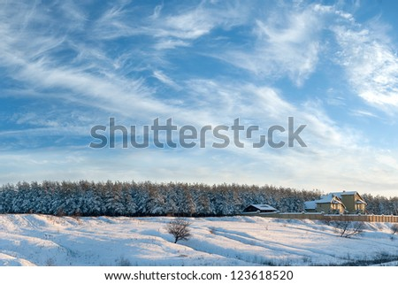 Winter landscape with the house on the edge of the wood, the trees is filled up with snow, beautiful sky - stock photo