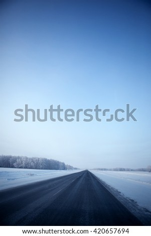 winter landscape with the road the forest and the blue sky