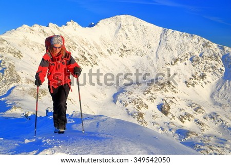 Winter landscape with woman mountaineer climbing snow covered trail, Retezat mountains, Romania - stock photo