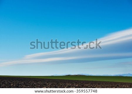Winter lanscape with blue sky, ploughed land and beautiful clouds