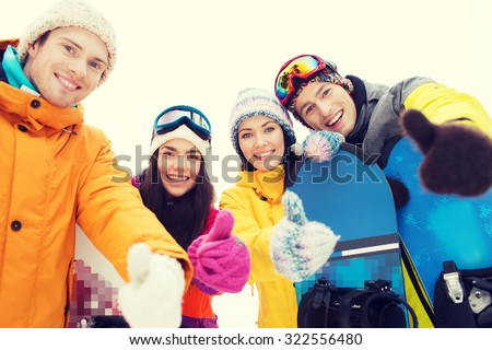 winter, leisure, extreme sport, friendship and people concept - happy friends with snowboards showing thumbs up - stock photo