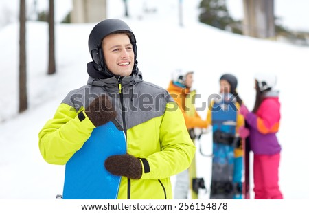 winter, leisure, extreme sport, friendship and people concept - happy young man in helmet with snowboard and group of friends - stock photo