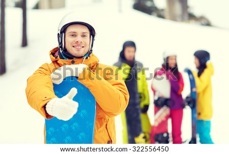 winter, leisure, extreme sport, friendship and people concept - happy young man in helmet with snowboard and group of friends showing thumbs up - stock photo