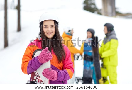 winter, leisure, extreme sport, friendship and people concept - happy young woman in helmet with snowboard and group of friends - stock photo