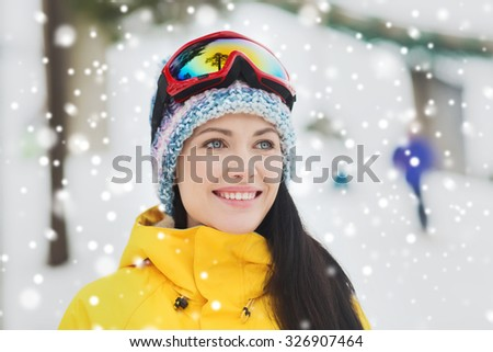 winter, leisure, sport and people concept - happy young woman in ski goggles outdoors - stock photo