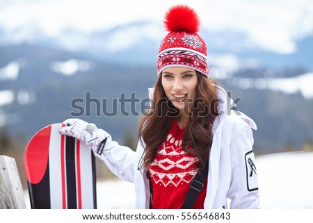 winter, leisure, sport and people concept - happy young woman in ski goggles outdoors