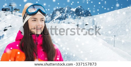 winter, leisure, sport and people concept - happy young woman in ski goggles over snow and mountain background