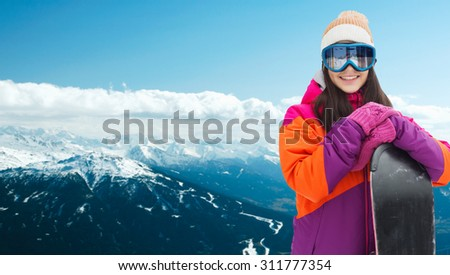 winter, leisure, sport and people concept - happy young woman in ski goggles with snowboard over snowy mountain background - stock photo