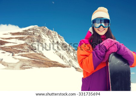 winter, leisure, sport and people concept - happy young woman in ski goggles with snowboard over snow and mountain background - stock photo