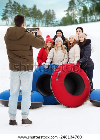 winter, leisure, sport, friendship and people concept - group of smiling friends with snow tubes taking picture by tablet pc computer outdoors - stock photo