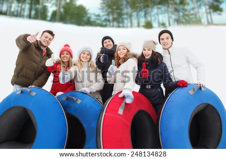winter, leisure, sport, friendship and people concept - group of smiling friends with snow tubes showing thumbs up outdoors - stock photo